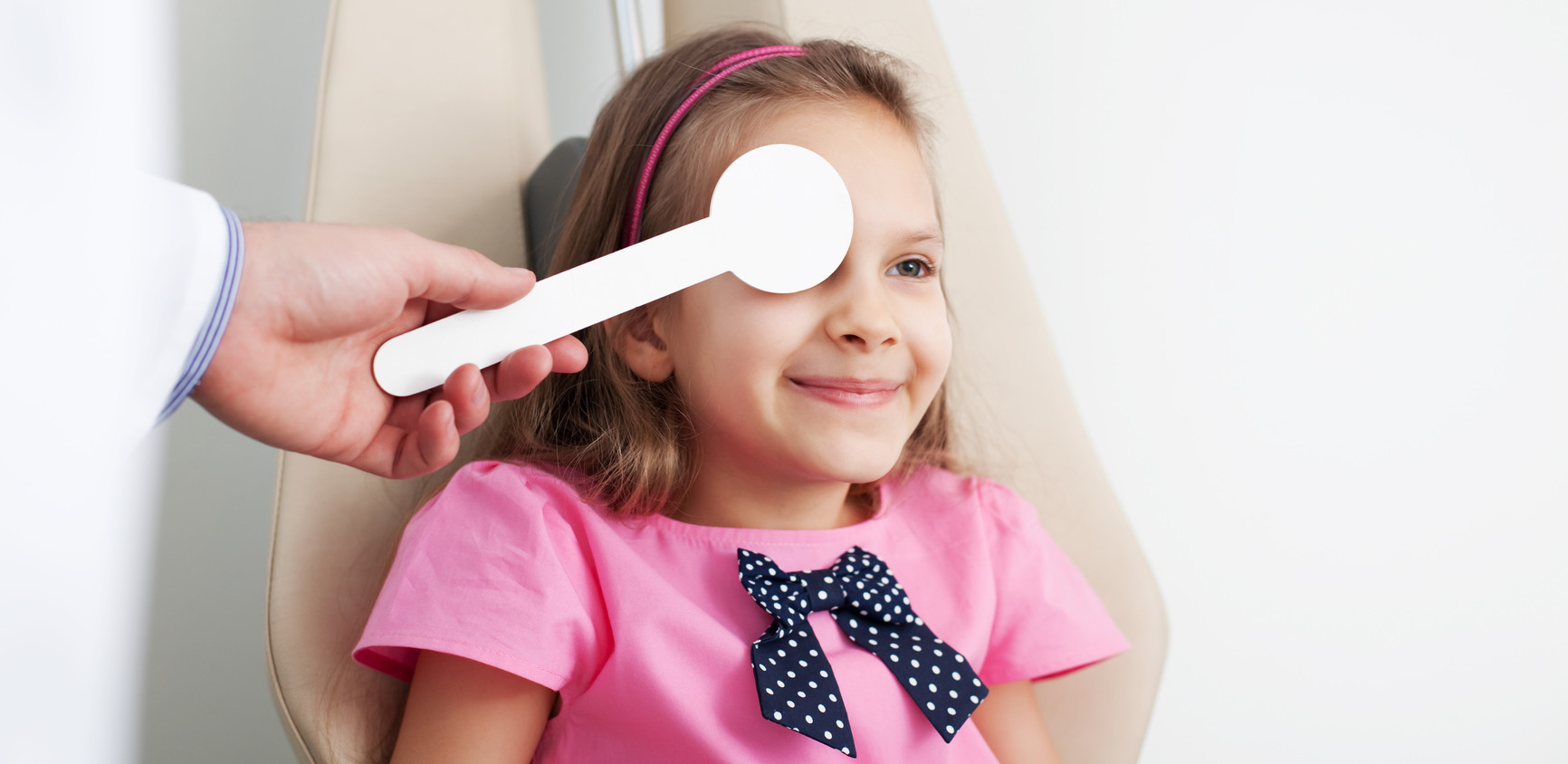Young girl is having eye exam performed by optician, optometrist or eye doctor.